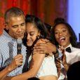 Barack Obama serrant dans ses bras sa fille Malia pour l'anniversaire de la jeune femme lors d'une fête célébrée à la Maison Blanche à Washington le 4 juillet 2016