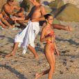 Bella Hadid, Jordan Barrett - Bella Hadid s'amuse avec ses amis sur une plage de Saint-Barthélemy le 7 décembre 2019. Après un shooting le mannequin américain se baigne et sirote son cocktail avec ses amies sur un paddle géant au couché du soleil.