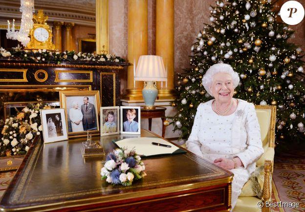 La reine Elizabeth II dans le salon 1844 au palais de Buckingham pour l'enregistrement de son allocution de Noël, le 25 décembre 2017. Sur le bureau à côté d'elle, des photos de George et Charlotte de Cambridge, de son mariage avec le prince Philip et de leurs noces de platine.  Dans la pièce figurait aussi une photo des fiançailles du prince Harry et Meghan Markle.