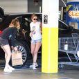 """Grâce à un agent de sécurité, Ashley Benson et Cara Delevingne évitent un fan les prenant en photo, alors qu'elles chargent leurs courses dans leur voiture. L'agent de sécurité a fait barrage à l'admirateur envahissant dans le parking du supermarché """"Erewhon"""" à Los Angeles, le 26 mars 2020."""