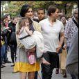 Suri Cruise dans les bras de sa maman : robe à pois ceinturée de noir, leggings noirs et... pas de chaussure ! Elle fait la grève apparemment... (Boston, 4 octobre 2009)