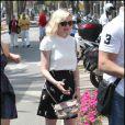 Petit pull blanc très bon chic bon genre, jupe noire imprimée griffée Miu Miu, ballerines aux pieds, et it-bag Chanel... Kirsten Dunst a fait un sans faute !