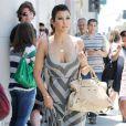 Kourtney Kardashian dans un style hippie très chic, avec une longuissime robe grise au décolleté ravageur, sans oublier ses sandales nude à tomber et son sac Motorcycle Balenciaga qu'on lui envie toutes.