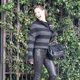 Kelly Brook semble ravie de son look cuir féminisé par un sac tendance.