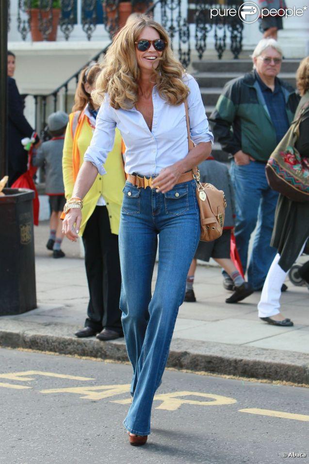 Vive les seventies ! Elle Macpherson est fabuleuse avec son jean Flare ultra-tendance, sa chemise blanche et ses compensés. Londres, 27 avril 2011