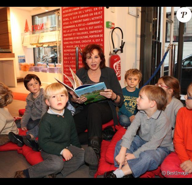 Marlène Jobert pose en compagnie d'enfants à la librairie Le Carré d'Encre, à Paris, le samedi 26 novembre 2011.