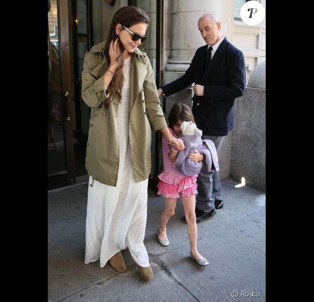 Katie Holmes semble amusée que sa fille Suri se cache des photographes à la sortie de leur appartement à Manhattan lors du 6e anniversaire de Suri le 18 avril 2012 à New York