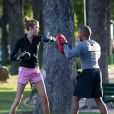 Le top model Karlie Kloss, en mini-short et baskets, pratique la boxe en plein air avec son coach dans un parc parisien. Le 28 septembre 2012.