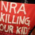 """Le vice-président de la NRA Wayne LaPierre est interrompu durant son discours à l'hôtel Willard par un manifestant qui tient un carré en tissu sur lequel est inscrit """"NRA Killing Our Kids"""". Washington, le 21 décembre 2012."""