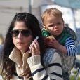 Selma Blair au téléphone et son fils Arthur dans les rues de Studio City, quartier de Los Angeles, le 7 février 2013. Arthur déguste une pomme.
