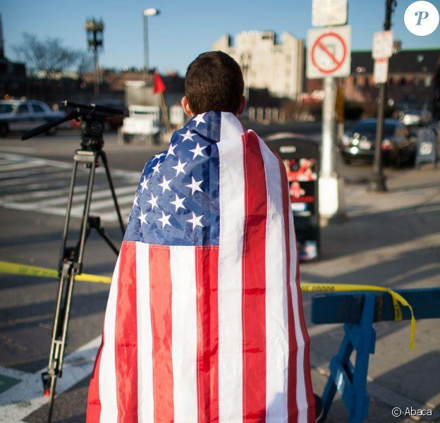 Image du drame du marathon de Boston qui a eu lieu le 15 avril 2013 : un étudiant porte le drapeau américain en hommage aux victimes