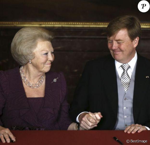 La main dans la main, un touchant passage de témoin respirant la confiance... La reine Beatrix des Pays-Bas signait le 30 avril 2013 à 10h10, en présence de membres du gouvernement dans le Mozeszaal du palais royal à Amsterdam, l'acte officiel d'abdication signifiant la fin de ses 33 ans de règne et l'intronisation de son fils le prince Willem-Alexander et son épouse Maxima.