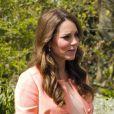 Kate Middleton, la duchesse de Cambridge enceinte et tout de corail vêtue, porte un manteau et une robe Tara Jarmon ainsi qu'une pochette et des souliers LK Bennett. Hampshire, le 29 avril 2013.