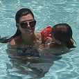 Kourtney Kardashian et Scott Disick se baignent dans une piscine avec leurs enfants Mason et Penelope a Miami, le 22 juillet 2013.  Please hide children's face prior to the publication Kourtney Kardashian spends the day with her family and friends at the pool in Miami, Florida on July 22, 2013.22/07/2013 - Miami