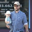 Jack Osbourne se promène, avec sa fille Pearl dans les bras, dans les rues de Los Angeles. Le 16 août 2013.