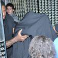 Justin Beiber sort du bordel Centauros, caché sous une couverture noire, à Rio de Janeiro, le 1er novembre 2013.