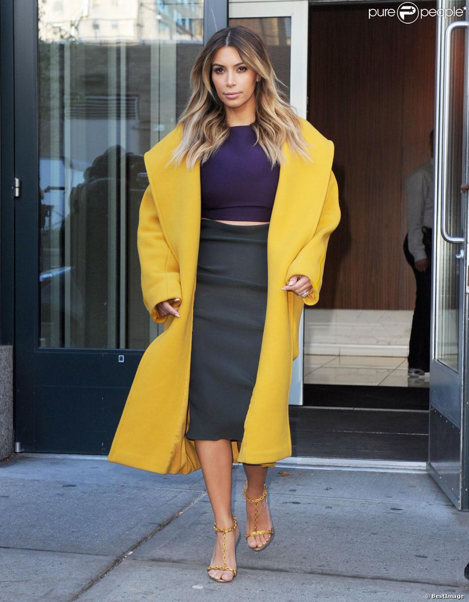 Kim Kardashian sort de l'appartement de son fiancé Kanye West à New York, habillée d'un manteau jaune en laine et angora Max Mara (collection automne-hiver 2013), d'un crop top violet, d'une jupe moulante Lanvin et de sandales Tom Ford. Le 20 novembre 2013.