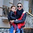 Miranda Kerr quitte son domicile en compagnie de son fils Flynn à New York, habillée de lunettes Prada, d'un perfecto Acne (modèle Merci Contrast), une chemise en jean nouée à la taille, un pantalon slim et des bottines noires. Le 16 novembre 2013.