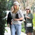 Rosie Huntington-Whiteley se rend dans un restaurant à Los Angeles, vêtue d'un sweater gris, d'une pochette à carreaux Chloé (modèle Lucy), d'un jean boyfriend Citizens of Humanity et de baskets Isabel Marant (modèle Betty). Le 17 novembre 2013.