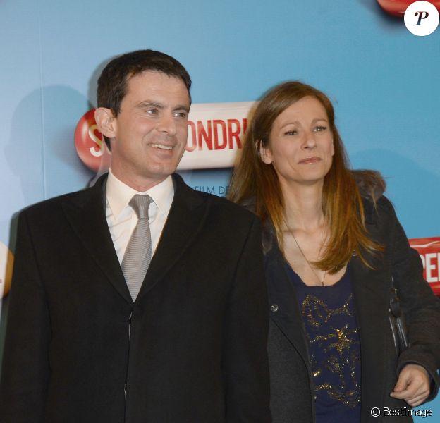 """Le ministre de l'Intérieur Manuel Valls et sa femme Anne Gravoin lors de l'avant-première du film """"Supercondriaque"""" au Gaumont Opéra à Paris, le 24 février 2014"""