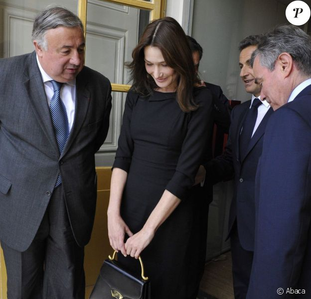 Carla Bruni-Sarkozy, suivie par son mari le président Nicolas Sarkozy, porte une robe noire L'Wren Scott au Château de Versailles. Juin 2009.
