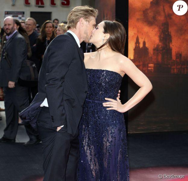 """Elizabeth Olsen et son compagnon Boyd Holbrook s'embrassent à la première du film """"Godzilla"""" à Londres le 11 mai 2014."""