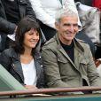Raymond Domenech et sa compagne Estelle Denis aux Internationaux de France de tennis de Roland Garros à Paris, le 27 mai 2014