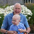 George H. W. Bush prend la pose avec Patrick (2 ans), fils de l'un de ses gardes du corps atteint d'une leucémie. En signe de solidarité, il s'est rasé la tête, comme une vingtaine d'agents de son service de sécurité, le 24 juillet 2013 à Kennebunkport.