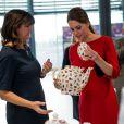 Kate Middleton découvre de la vaisselle vendue au profit de la campagne de l'EACH. La duchesse de Cambridge, enceinte de quatre mois, dévoilait ses rondeurs dans une robe Katherine Hooker alors qu'elle se mobilisait le 25 novembre 2014 à Norwich, dans le Norfolk, pour lancer une levée de fonds en vue de construire un nouvel hôpital pour enfants de l'organisme East Anglia Children's Hospices.