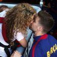 Shakira embrasse Gerard Piqué au Camp Nou le 18 avril 2015 lors du match FC Barcelone - FC Valence. Aidée par sa belle-mère Montserrat Bernabeu, elle était venue avec ses enfants Milan (2 ans) et Sasha (3 mois) encourager son chéri.