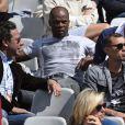 Brahim Asloum et Sylvain Wiltord dans les tribunes de Roland-Garros pour soutenir Clothilde de Bernardi, la compagne de l'ex-boxeur, le 21 mai 2005 à Paris