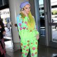 Kesha, les cheveux jaune, arrive à l'aéroport de LAX pour prendre l'avion. La coque de téléphone de Kesha est une poupée en 3D! Le 4 juillet 2015