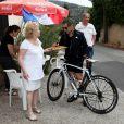 L'ancien président de la république, Nicolas Sarkozy, fait escale chez Ginette qui lui fait goûter ses beignets lors d'une sortie à vélo dans la forêt des Maures, Le Lavandou, le 7 juillet 2014 lors de ces vacances dans la résidence de sa belle famille au domaine du Cap Nègre.