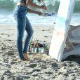 Emily Ratajkowski fait de la peinture sur la plage de Malibu, habillée d'un haut et d'un jean American Eagle. Los Angeles, le 16 août 2016.