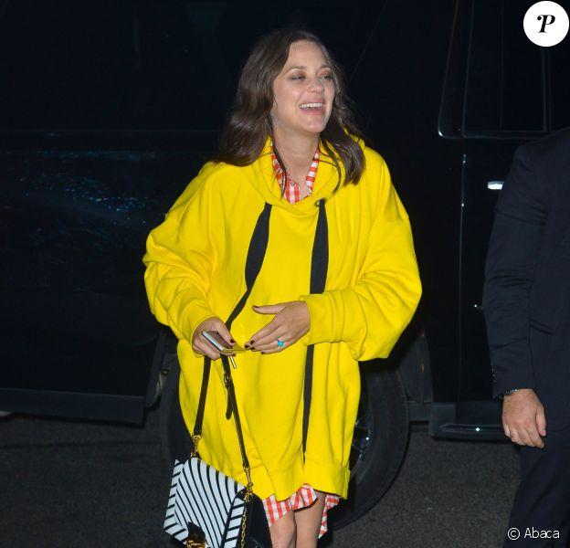 Marion Cotillard, enceinte à New York, porte un pull à capuche jaune et une chemise à carreaux Marques Almeida (collection automne-hiver 2016-17), et des bottines Louis Vuitton (collection printemps-été 2017). Le 16 novembre 2016.
