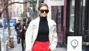 "Gigi Hadid à New York, porte un trench-coat AMBUSH® (collection ""Surplus Sound System""), un pull Wolford, un pantalon rouge et des chaussures Tony Blanco. Le 13 février 2017."