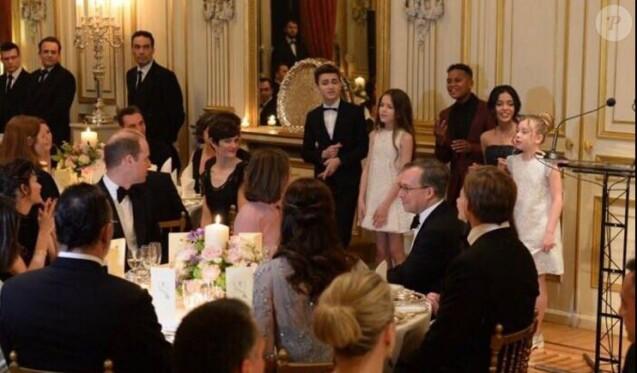 Le prince William et Kate Middleton observant les Kids United en train de chanter leur reprise du tube Happy lors du dîner de gala organisé le 17 mars 2017 à la résidence de l'ambassadeur de Grande-Bretagne à Paris, au premier soir de la visite officielle du duc et de la duchesse de Cambridge. Happy, l'une des chansons au son desquelles le prince William se déchaînait quelques jours plus tôt à Verbier...