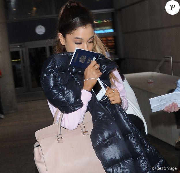 Ariana Grande se cache des photographes à son arrivée à l'aéroport de LAX à Los Angeles, le 3 juillet 2015