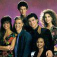 """La jolie Elizabeth Berkley, entourée de tous ses camarades de """"Sauvés par le Gong"""", aux débuts des années 90."""
