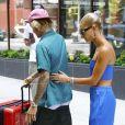 Justin Bieber et sa fiancée Hailey Baldwin sortent d'un immeuble avec des bagages et saluent leurs fans avant de monter dans une voiture à New York, le 13 juillet 2018