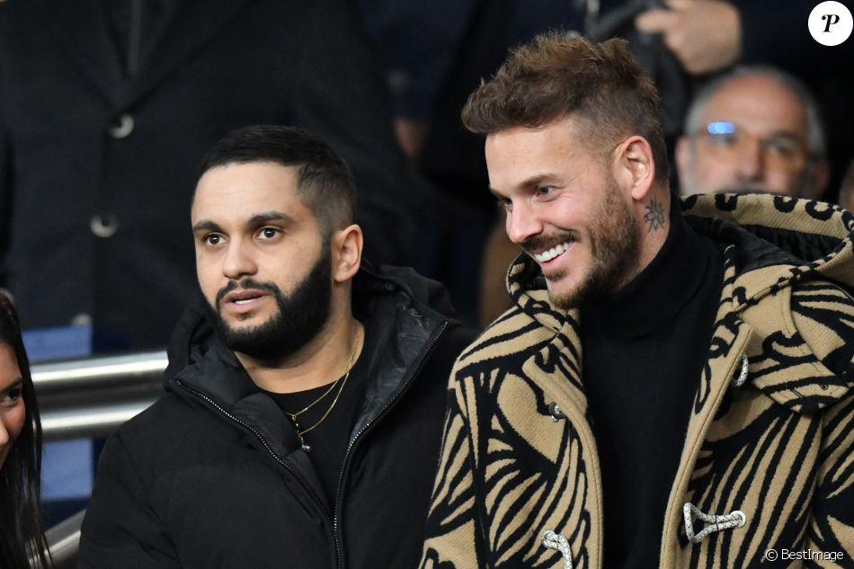 Malik Bentalha et Matt Pokora (M. Pokora) dans les tribunes du parc des Princes lors du match de football de ligue 1, opposant le Paris Saint-Germain (PSG) contre l'Olympique de Marseille (OM) à Paris, France, le 17 mars 2019.
