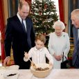 Le prince George de Cambridge prépare, sous le regard bienveillant du prince William, duc de Cambridge, du prince Charles, prince de Galles et de la reine Elisabeth II, des puddings de Noël, dans le cadre du lancement de l'initiative 'Together at Christmas' de la Royal British Legion au Palais de Buckingham, le 21 décembre 2019.