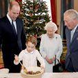 Le prince George de Cambridge prépare, sous le regard bienveillant du prince William, duc de Cambridge, du prince Charles, prince de Galles et de la reine Elisabeth II, des puddings de Noël, dans le cadre du lancement de l'initiative 'Together at Christmas' de la Royal British Legion au Palais de Buckingham, le 21 décembre 2019.