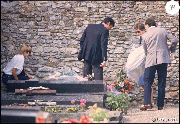 Alain Delon et sa compagne Mireille Darc sur la tombe de Romy Schneider quelques jours après ses obsèques, en juin 1982, à Boissy-sans-Avoir, dans les Yvelines.