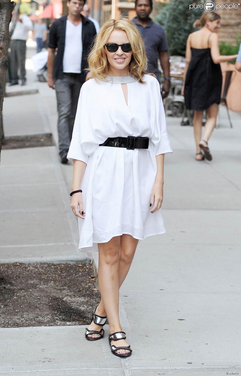 La chanteuse Kylie Minogue très chic et estival dans une petite robe  blanche façon tunique, joliment rehaussée d une large ceinture noire,  portée avec de ... 9f255d47a9a