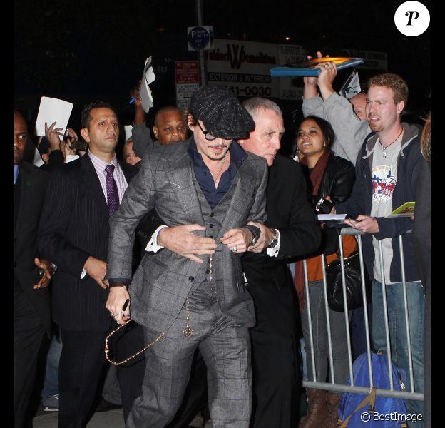 Johnny Depp escorté par son garde du corps, à New York le 25 octobre 2011 pour la projection de Rhum Express