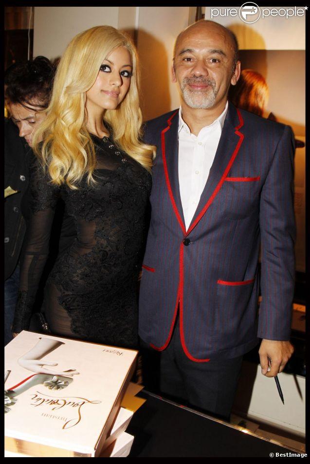 Zahia Dehar a pris la pose avec Christian Louboutin lors de la présentation des photos du livre du chausseur à la galerie du Passage à Paris le 21 novembre 2011
