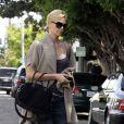 L'actrice Charlize Theron et son sac Givenchy, porté en accessoire avec des chaussures en daim Loft. Los Angeles, le 7 mars 2011.