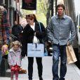 Essayant de cacher son ventre, Alyson Hannigan se promène avec son mari Alexis Denisof et leur fille Satyana à New York le 10 avril 2012