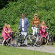 Pour les photographes, les royaux ont simulé une balade à vélo. Le prince Willem-Alexander et le princesse Maxima des Pays-Bas, comme chaque année, ont pris la pose avec leurs filles les princesses Catharaina-Amalia, Alexia et Ariane, désormais âgées de 8, 7 et 5 ans, pour fêter l'arrivée des vacances d'été. Le 7 juillet 2012, la séance photo a eu lieu dans le parc de la résidence familiale à Wassenaar, la villa Eikenhorst.